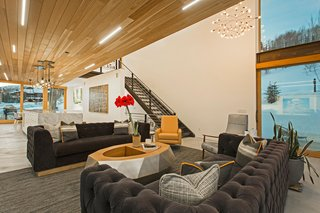 A Plunging Roof Carves Out Space in This Park City Home Offered at $2.4M - Photo 2 of 9 - Mullin discovered the Cirrus Linear LED lights in the red cedar wood ceiling at Dwell on Design in Los Angeles in 2015. Cold-rolled steel stairs lead to the upper level and add a touch of industrialism to the space. Adjacent to the living room is a large outdoor balcony, accessible through disappearing sliding glass doors.