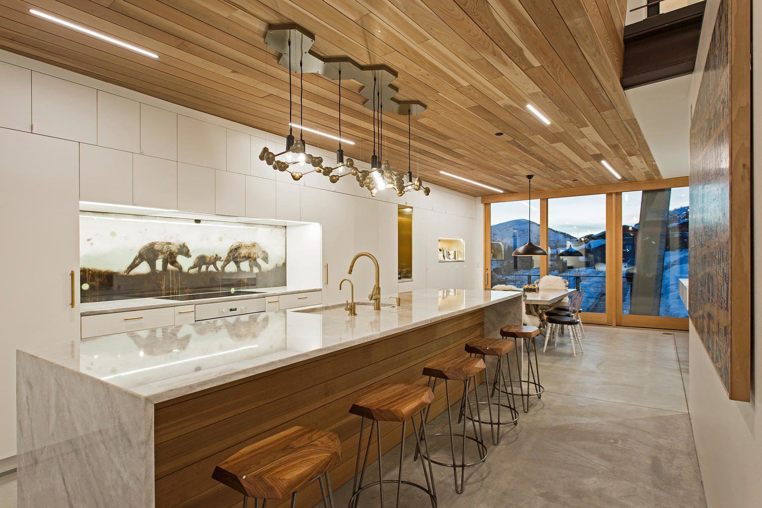 A chandelier by artist Joe Norman provides a dramatic accent to the kitchen and dining areas. The backsplash was a commission by the artist KOLABS, part of Mullin's wife's gallery. Tagged: Kitchen, Marble Counter, Wood Counter, White Cabinet, and Pendant Lighting.  Photo 5 of 10 in A Plunging Roof Carves Out Space in This Park City Home Offered at $2.4M