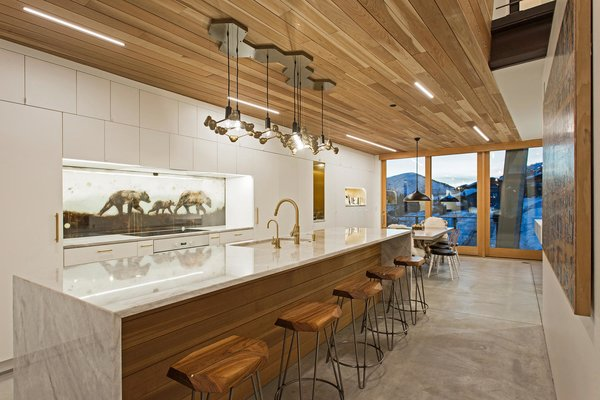 A chandelier by artist Joe Norman provides a dramatic accent to the kitchen and dining areas. The backsplash was a commission by the artist KOLABS, part of Mullin's wife's gallery.