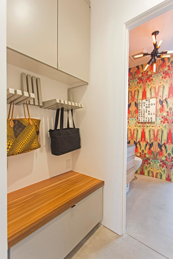A clever storage area holds purses and bags, while a bench hides away bulkier items.  Photo 9 of 10 in A Plunging Roof Carves Out Space in This Park City Home Offered at $2.4M