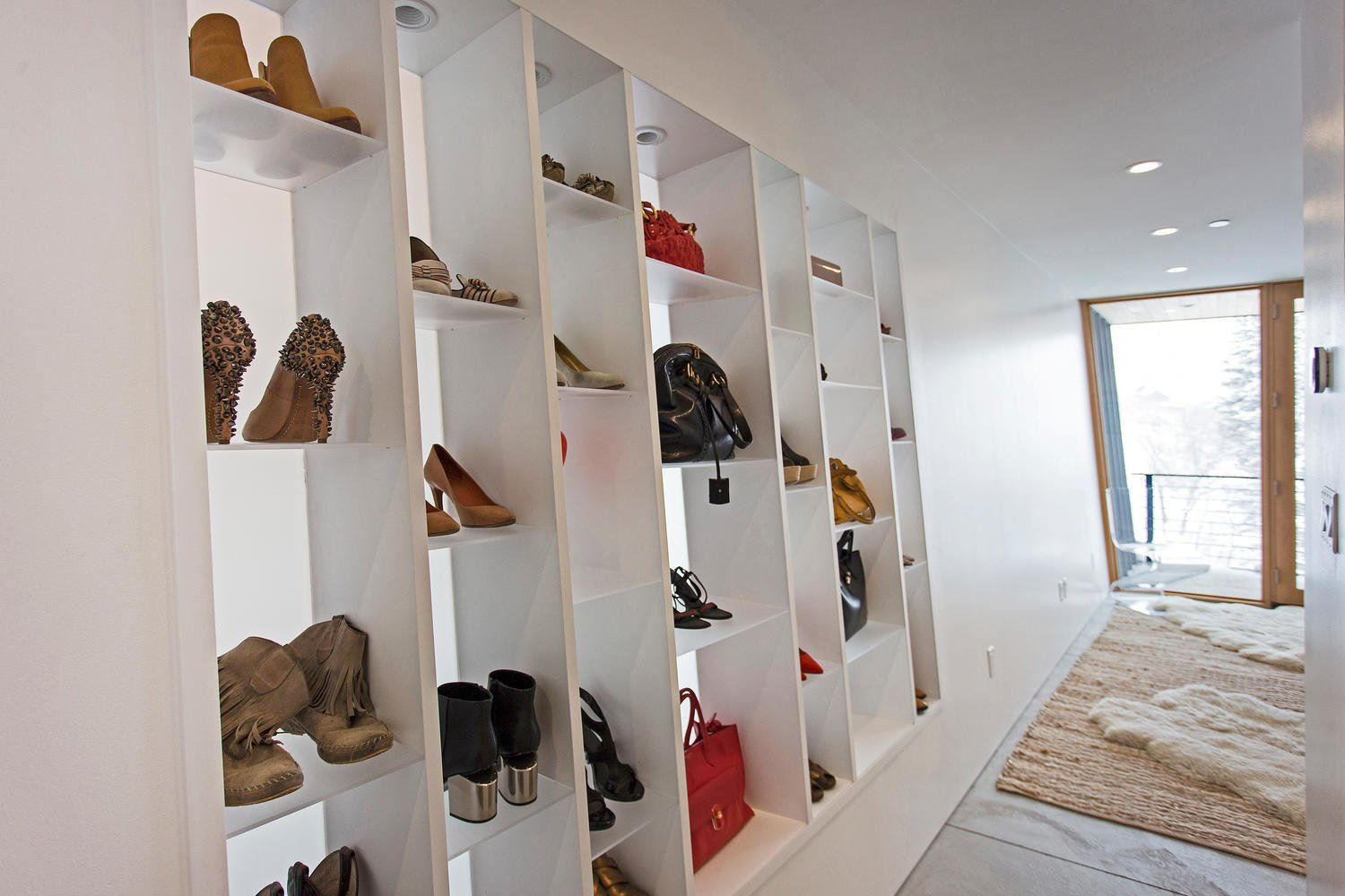 The multipurpose, built-in shelves in the master bedroom can hold shoes, accessories, books, or decor.  Photo 8 of 10 in A Plunging Roof Carves Out Space in This Park City Home Offered at $2.4M