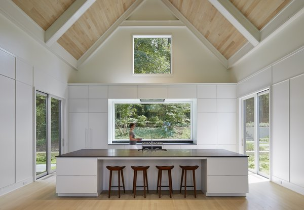 "Two smaller sliding doors lead outward from the kitchen, which continues the home's minimalist aesthetic. Booth Hansen chose to paint the window interiors white to match the neutral color palette. ""When you're looking out the windows, the house takes a backseat to the environment,"" says Sandschafer."