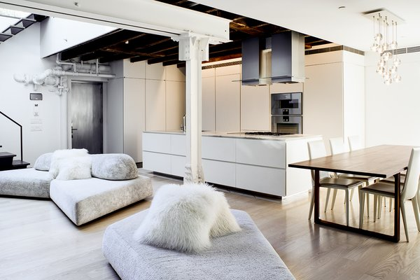 """The minimalist, open kitchen was built into freestanding millwork walls. Valgora strove to layer design elements from the 19th, 20th, and 21st centuries. """"Old growth wooden beams and angled timber columns from 1869 are exposed with riveted steel columns and tangles of pipes and infrastructure from the 1920s conversion to a factory,"""" he points out. A modular On the Rocks sofa by designer Francesco Binfare breaks up the space and transitions into the living room."""