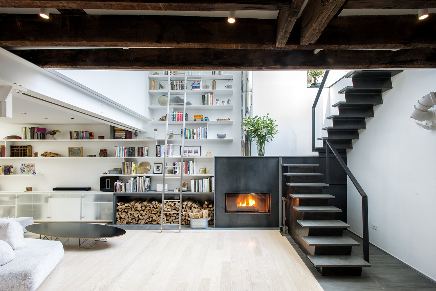 Tagged: Living Room, Storage, Ceiling Lighting, Coffee Tables, Shelves, Wood Burning Fireplace, Light Hardwood Floor, Sofa, and Bookcase.  Photo 1 of 10 in A Rooftop Addition on a 19th-Century Building Suits a Growing Family's Needs