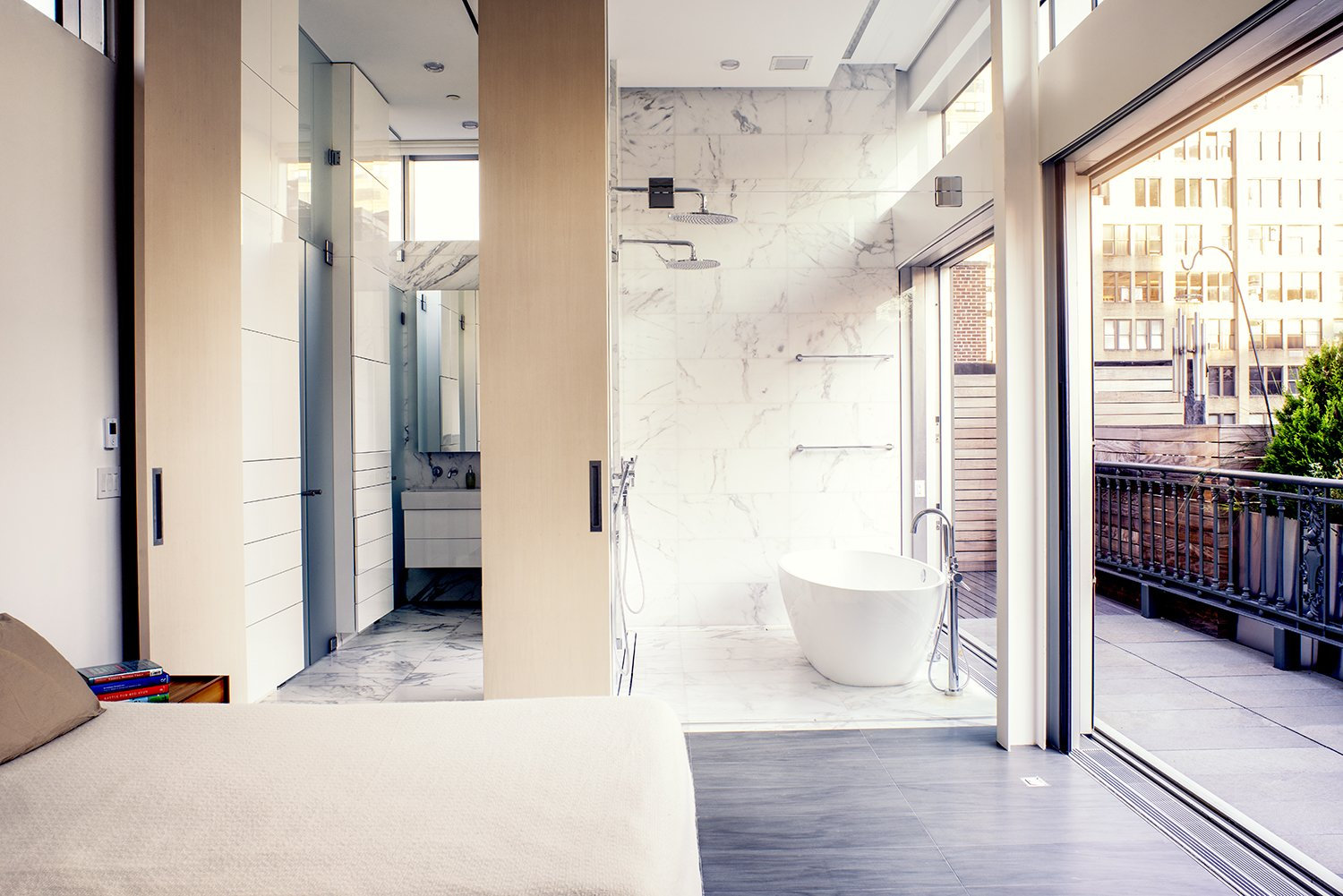 A marble wet room features a freestanding tub by Victoria and Albert and dual showers, while another shower on the terrace offers the option of washing outdoors. A 12-foot wooden door swings back to reveal a dressing room. Tagged: Bath Room, Freestanding Tub, and Marble Wall.  Photo 7 of 10 in A Rooftop Addition on a 19th-Century Building Suits a Growing Family's Needs