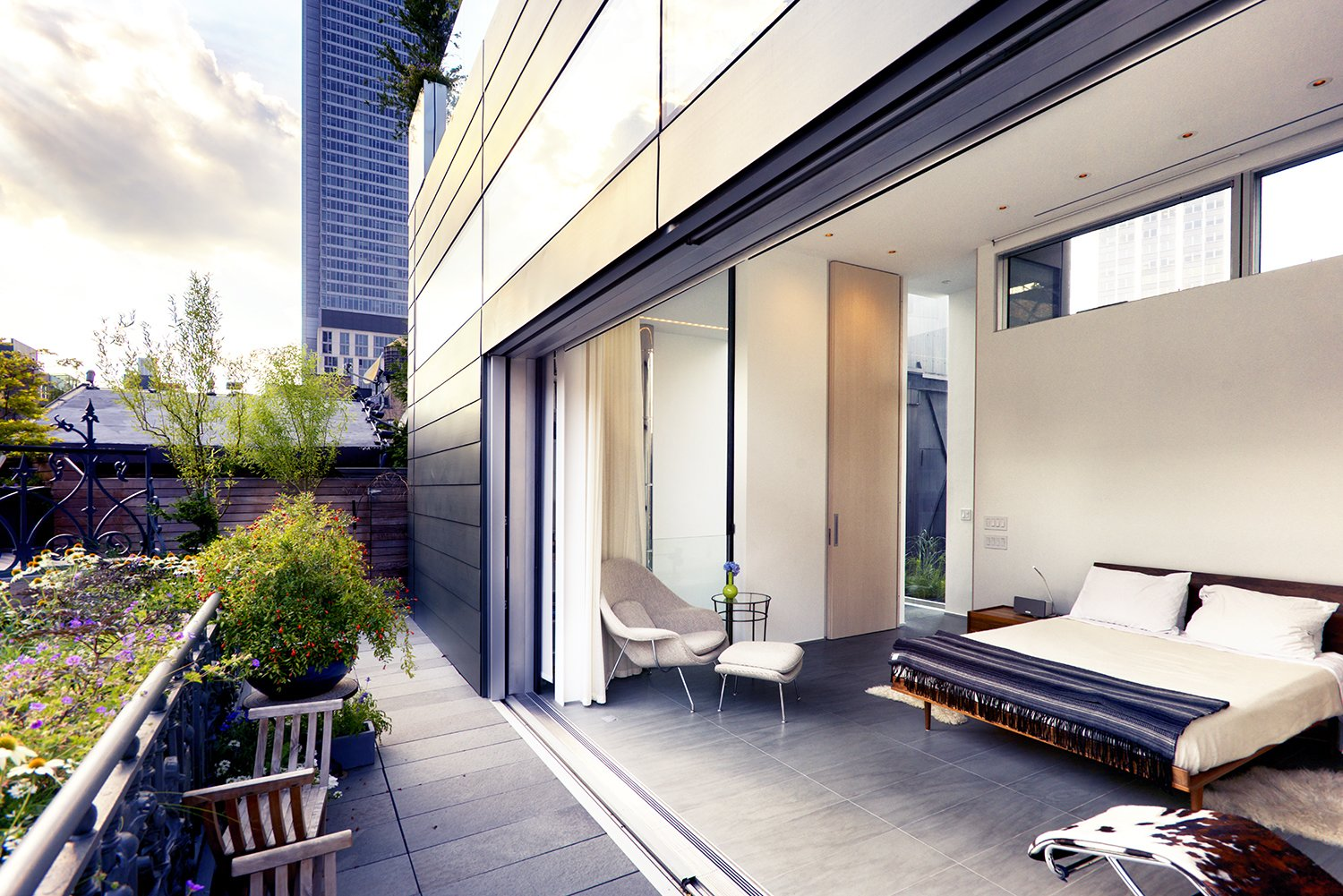 An expansive sliding glass door retracts into the zinc facade, opening up the master suite to a garden terrace. This echoes a 15-foot Corian wall that transforms a children's bedroom into an entertainment space, allowing flexibility and anticipating the time when the boys leave for college. Tagged: Bedroom, Bed, Chair, Recessed Lighting, and Night Stands.  Best Photos from A Rooftop Addition on a 19th-Century Building Suits a Growing Family's Needs