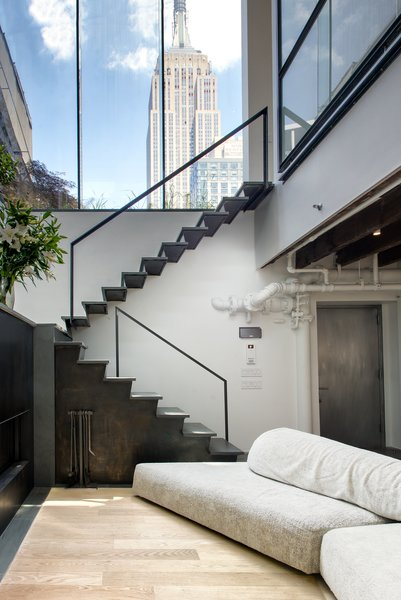 A blackened steel staircase by Delform leads to the upper level. A tall glass clerestory frames views of the Empire State Building and reinforces the indoor/outdoor motif