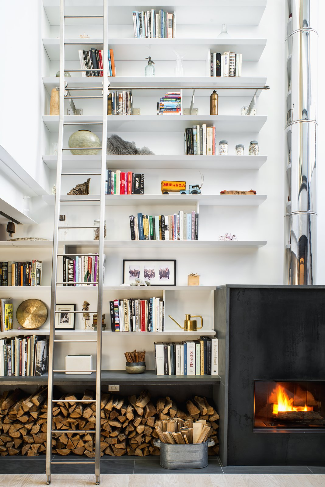 The double-height living room provided the perfect opportunity to combine the homeowners' love of art, literature, and travel, allowing them to fill the 24-foot shelves with books and collected artifacts. A wood-burning sustainable fireplace by Wittus adds a broad stroke of warmth.