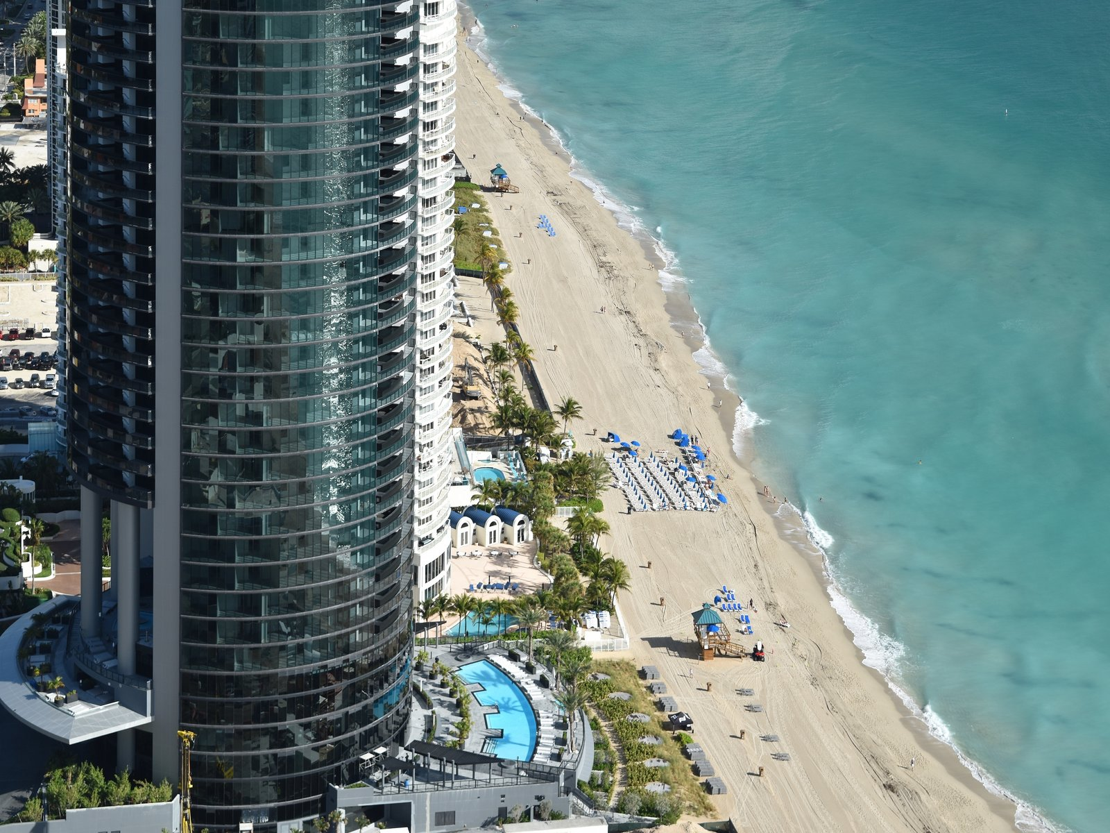 Soaring 650 feet in the air, Porsche Design Tower Miami is currently the tallest building on Sunny Isles Beach. This aerial view shows the landscaped pool deck and the sunset terrace.  Photo 2 of 11 in Porsche Design's Lavish Residential Tower in Miami Lifts Residents and Cars Sky High