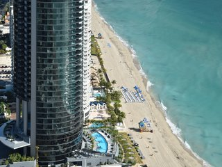 Soaring 650 feet in the air, Porsche Design Tower Miami is currently the tallest building on Sunny Isles Beach. This aerial view shows the landscaped pool deck and the sunset terrace.