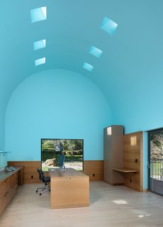 "The office boasts an 18-foot, barrel-vaulted ceiling, an architectural metaphor for inspiration and exaltation. Despite only visiting the site once before embarking on the four-year design process, Sottsass precisely placed picture windows to frame available views. ""The windows are not done classically,"" explains Michael Dreyfus, CEO of Dreyfus Sotheby's International Realty. ""You can't see out of them except when you're in front of them. David literally has to stop to see outside."" The old oak tree that used to stand outside fell a few years ago, but the rock preserves a sense of deliberate placement."