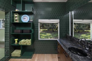 The master bathroom forges a connection to the outdoors through dark, forest green tile.