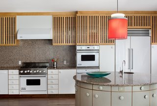Oversized knobs add a whimsical touch to the kitchen, where a pendant designed by Johanna Grawunder—who worked with Sottsass in Milan—hangs over the circular island. White Viking appliances are integrated with the cabinetry.