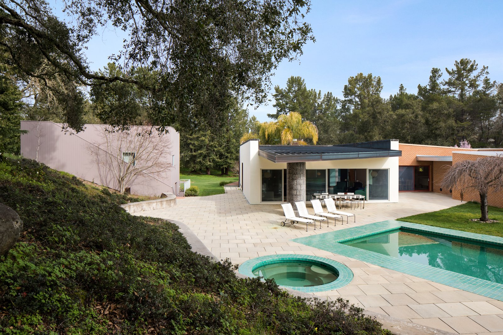 The pool and outdoor hot tub bounce green light off the roof hanging over the back terrace, creating a lush environment.  Photo 10 of 12 in IDEO Founder David Kelley Asks $15M For His Ettore Sottsass-Designed Masterpiece