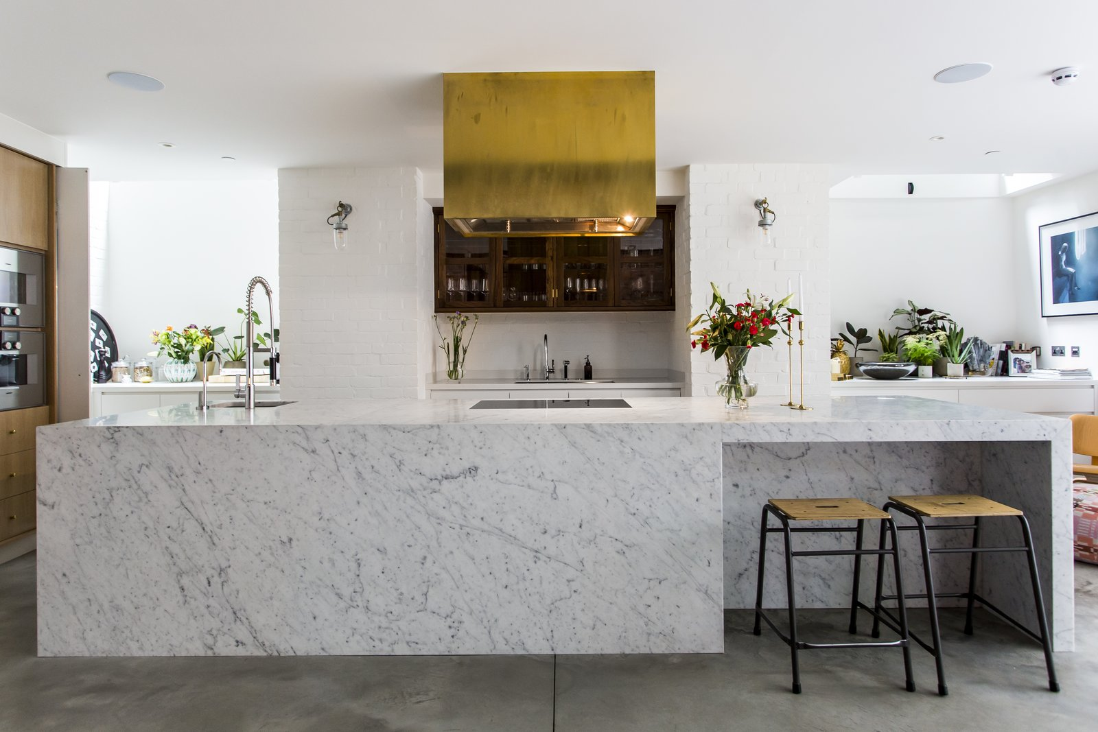 Brass finishings and an eye-catching range hood contrast with cool Carrara marble.  Photo 6 of 8 in Stay in a Converted Victorian Cooperage in London
