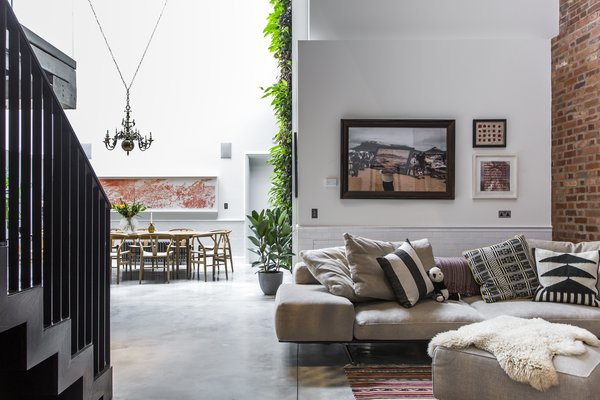 Interior designer Andrea Larsson Sanchez complements the polished concrete floor, original Crittall windows, and exposed brick with contemporary furnishings and graphic textiles.