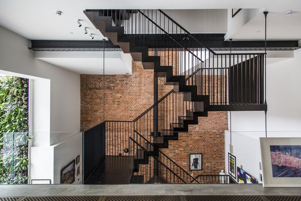 Entering the apartment from the street level, guests meet a dramatic, three-story atrium and a feature staircase. A glass balustrade heightens the effect. Tagged: Staircase, Metal Railing, and Metal Tread.  Photo 2 of 8 in Stay in a Converted Victorian Cooperage in London