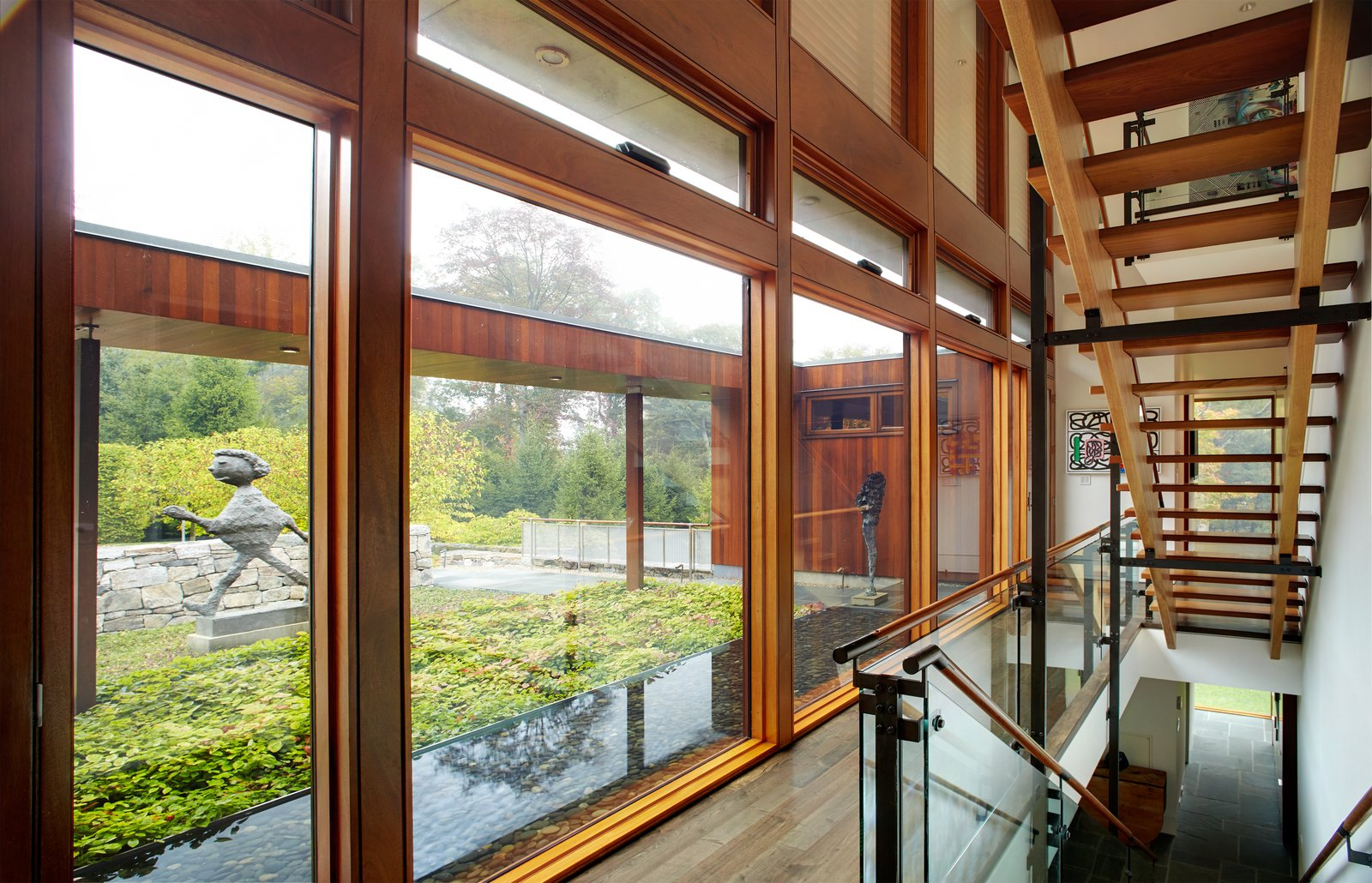 A two-story glass curtain wall allows for natural light and views to permeate the space and the open stairs.  Photo 3 of 8 in An Eliot Noyes Transformation in Connecticut Honors the Experimental Spirit of the Original