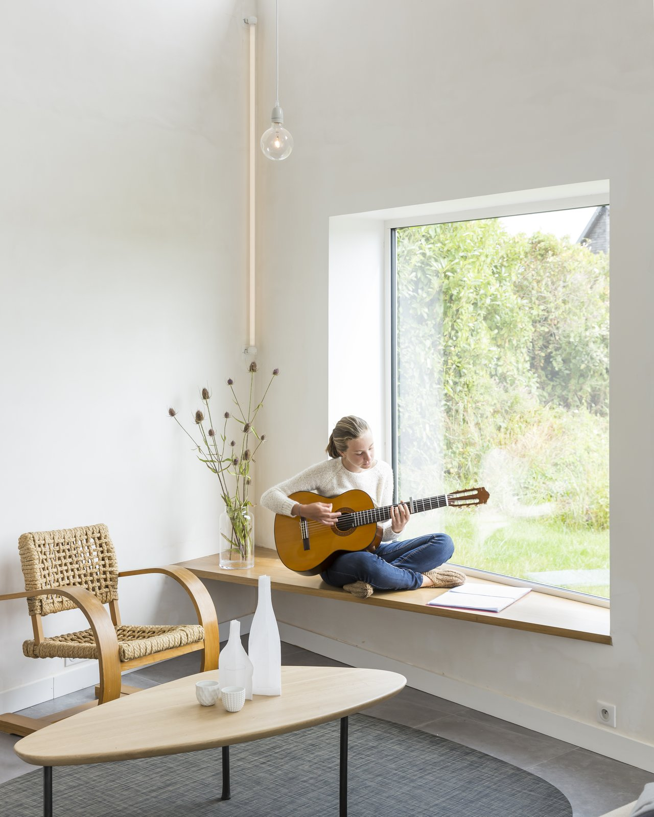 A bench by a window on the southern facade provides a sunny perch for reading, sipping coffee, or playing guitar.  Photo 4 of 10 in Framing the Landscape and Capturing Light, a Photographer's Home and Studio Echoes His Work