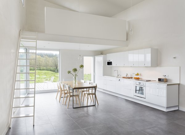 A sleek, minimal kitchen with lacquered MDF cabinets provides a glossy contrast to the unpainted walls.