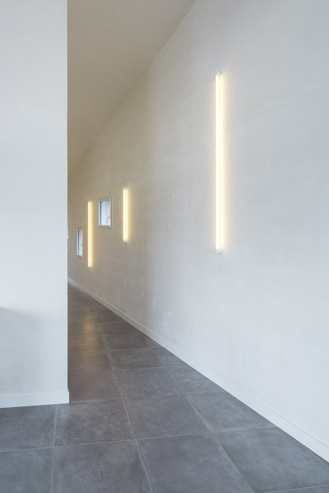 From a constricted entryway without a lot of natural light, the passageway fans upwards towards the landscape. Throughout the home, simple neon lights on unpainted plaster walls produce a warm glow. Explains Alireza Razavi, director of Studio Razavi Architecture,  Photo 2 of 10 in Framing the Landscape and Capturing Light, a Photographer's Home and Studio Echoes His Work