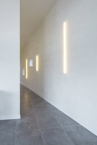 "From a constricted entryway without a lot of natural light, the passageway fans upwards towards the landscape. Throughout the home, simple neon lights on unpainted plaster walls produce a warm glow. Explains Alireza Razavi, director of Studio Razavi Architecture, ""The Dan Flavin-ist quality of the neon bulbs perfectly lit the space without focusing your attention on the fixture."""