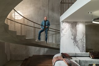 Here's How Hollywood Builds a Malibu Dream Home—on a Vancouver Soundstage - Photo 3 of 10 - Above, Novotny surveys the set. The concrete walls and floors were created by pouring a quarter-inch layer of concrete over plywood. While marble is traditionally painted for film and television sets, Novotny took a different route to save time. After hunting down the perfect slab of Calacatta marble in a showroom, he hired a photographer to capture a high-resolution image that was then printed on sheets of white plastic by Astek Wallcovering in Los Angeles.