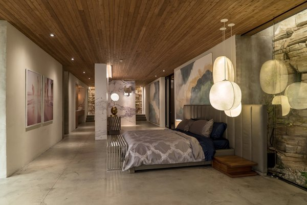 Kyle West's bedroom features an arrangement of Mori pendant lights by Rich Brilliant Willing and the Oviedo Leather Chair by Restoration Hardware, not pictured. A cloud mural painted by local artist Graeme Berglund contributes to an airy atmosphere.