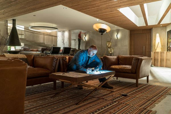 Real cedar planks line the ceilings. Novotny works in the television area, which features Sorensen Leather Chairs by Restoration Hardware, the Torme Floor Lamp by Mr. Brown, and IKEA rugs.