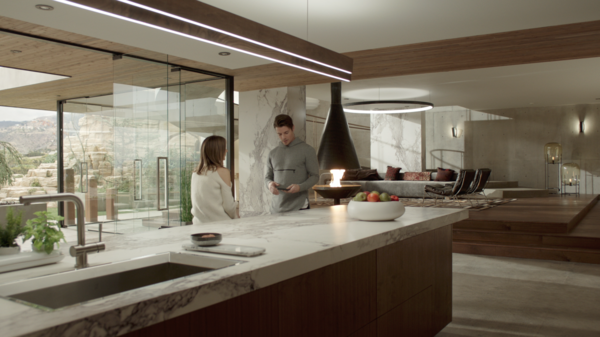 """Kyle West and Megan Morrison, played by actress Christine Evangelista, have a conversation in the kitchen, which boasts walnut veneers. The glass panels that offer """"oceanfront"""" views are each three feet wide, and are held with a strip of metal that allows the panel to spin—which comes in handy to manipulate reflections during filming."""