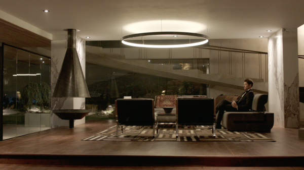 Kyle West, portrayed by actor Josh Henderson, sits in the living room of his home. Set decorator Renee Read outfitted the space with a custom couch that was originally made for the film Fifty Shades of Grey, the Nicholas Square Coffee Table by Restoration Hardware, the Nova Side Table by CB2 in collaboration with Kravitz Design, and Cammeo chairs by Natuzzi.