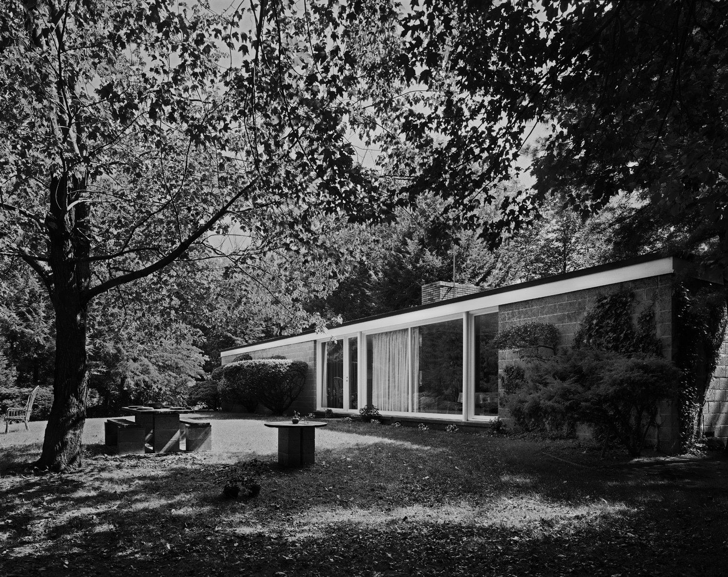A 1976 photo by Robert Damora shows the Booth House in its forested setting. Robert, who developed techniques to capture a sense of space and volume, was once hailed by Walter Gropius as