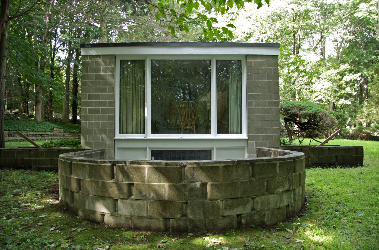 A large window from the bedroom overlooks the sunken terrace that allows the basement-level studio to open to the outside.  Photo 7 of 10 in With $1 Million, You Can Save Philip Johnson's First Commissioned House