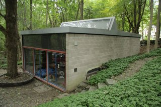 Built in the early 60s, the separate concrete-and-glass studio echoes the original home.