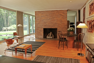 """Reminiscent of the Glass House, a monumental brick fireplace stands in the center of the living room. """"Because the home was designed for a couple without children, it's a very large, open space that was signature of the modern experiments at the time,"""" says Matthew."""