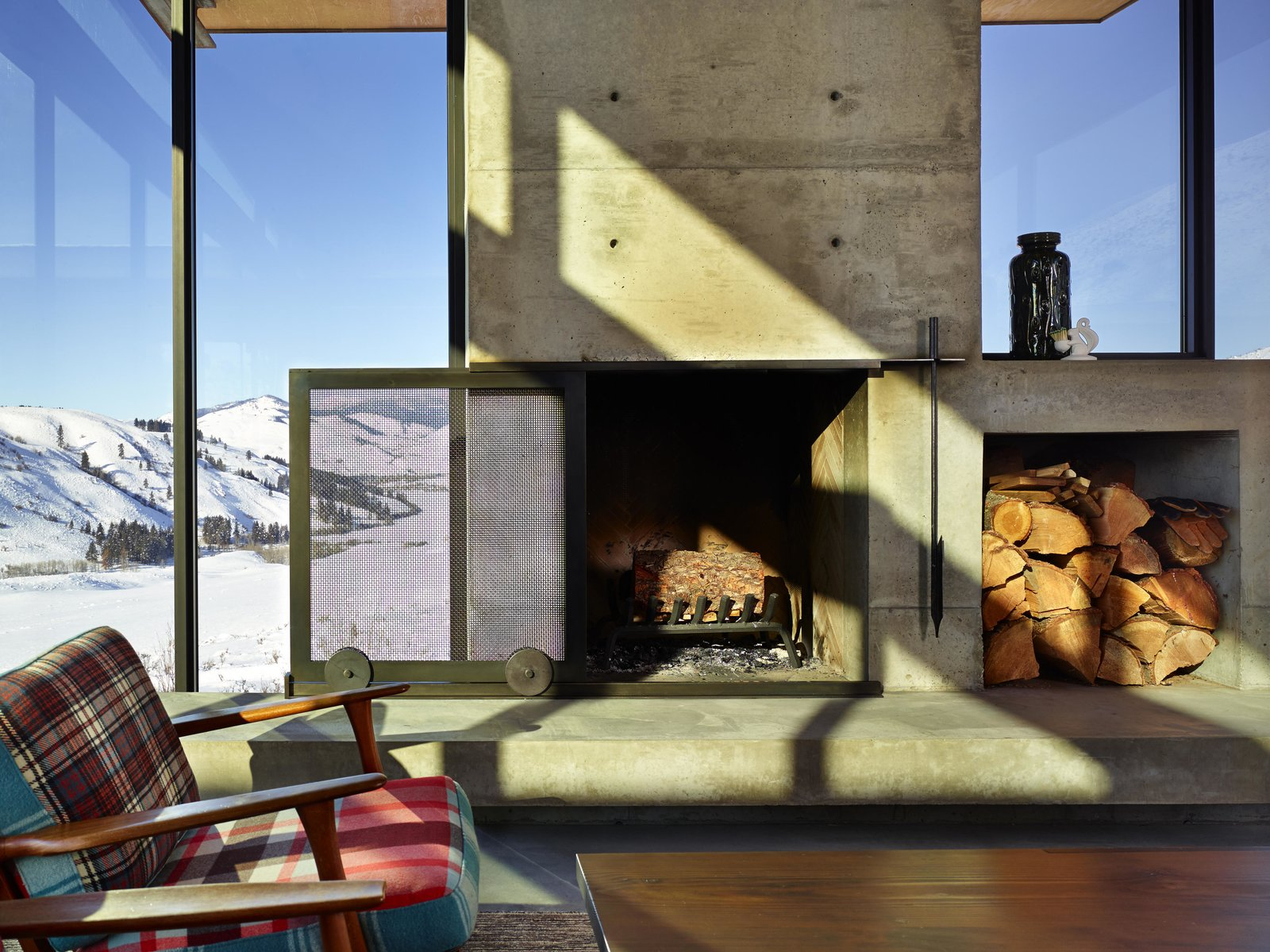 A sliding mesh screen glides over the fireplace, which features a built-in cubby for a stockpile of wood. Tagged: Living Room, Standard Layout Fireplace, and Chair.  Photo 4 of 11 in A Steel-and-Glass Compound Is One Family's Launchpad For Adventure