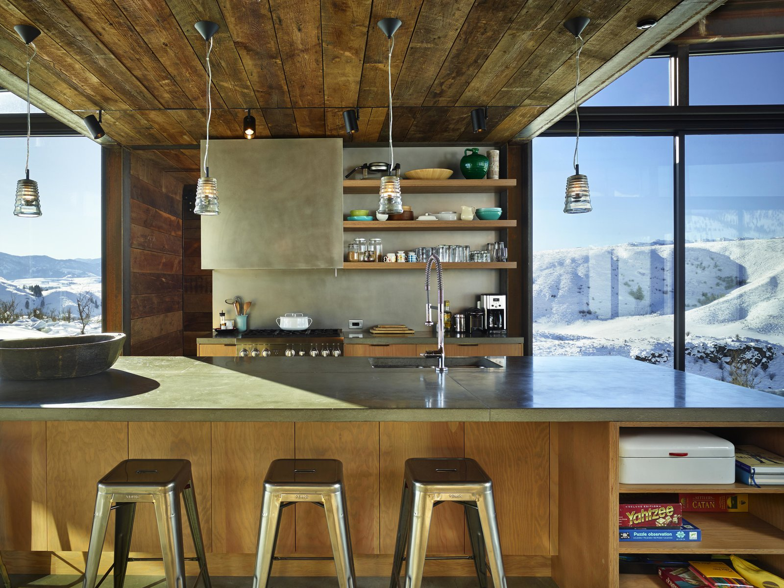Wood siding salvaged from an old barn in Spokane, Washington, was repurposed for the project. Tagged: Kitchen, Concrete Counter, Wood Cabinet, and Pendant Lighting.  Photo 5 of 11 in A Steel-and-Glass Compound Is One Family's Launchpad For Adventure