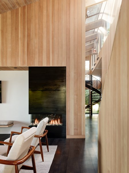 The living room Ortal fireplace is clad in cold-rolled steel with a waxed finish. The side chairs, vintage reproductions from Room and Board, feature shapely walnut arms.
