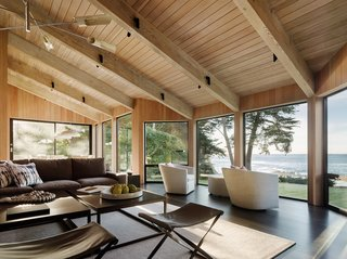 50 Modern Homes With Floor-to-Ceiling Windows - Photo 30 of 50 - In keeping with the philosophy of Sea Ranch, the four-year remodel and addition honors the landscape and emphasizes a sense of place through material integrity. Vertical grain, clear cedar siding clads the exterior while clear fir wraps the interior, and floor-to-ceiling windows offer stunning glimpses of the sea and surrounding meadows. The living room furniture includes leather-finished black granite coffee tables, designed as two pieces to break up the scale, and Siren pendants by David Weeks Studios which recall the mobiles of Alexander Calder.