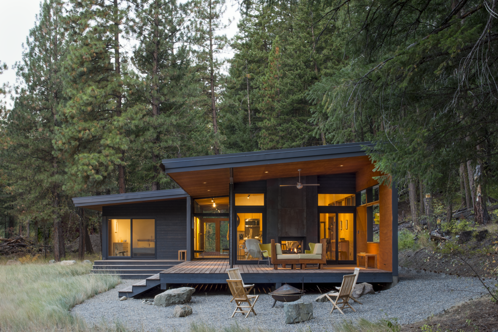 In Washington's Methow Valley, a modern cabin with an outdoor living room allows views of the surrounding woodland and meadow to perforate its volume.   By day, the Chechaquo Lot 6 cabin gives the impression of floating in a forest clearing; by night, its windows glow against the wooded darkness. From all vantage points, the landscape permeates this 1,000-square-foot cabin, designed for two outdoor enthusiasts and tucked at the toe of a dramatic slope in Winthrop, Washington. Tagged: Exterior, Cabin Building Type, Wood Siding Material, and Glass Siding Material.  Photo 2 of 10 in A Lean Cabin in Washington Dismantles the Indoor/Outdoor Divide
