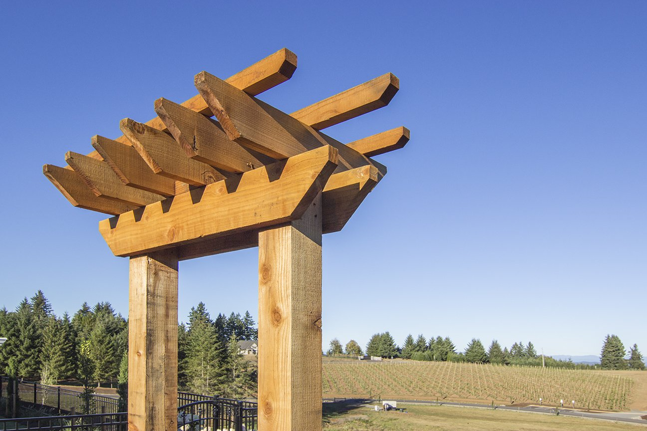 Redwood arbors feature two posts connected by a cross piece. Besides adding visual interest to an exterior space, they can also be built with a gate, bench, or planter box for added functionality.  Photo 7 of 7 in Sustainable Redwood Stars in an Oregon Architectural Showcase