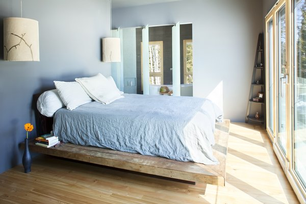 Modern home with bedroom, bed, pendant lighting, and light hardwood floor. The master bedroom, which looks out through a wall of glass at the Whitefish Range, benefits from solar tubes that let in additional light. Center-mounted glass panels pivot to let you into the master bath. Photo 7 of 534 Twin Bridges Road