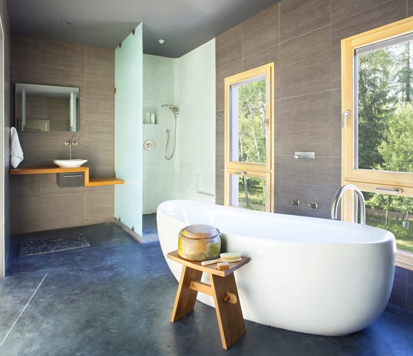 A deep soaking tub offers relaxation and views of the surrounding foliage.