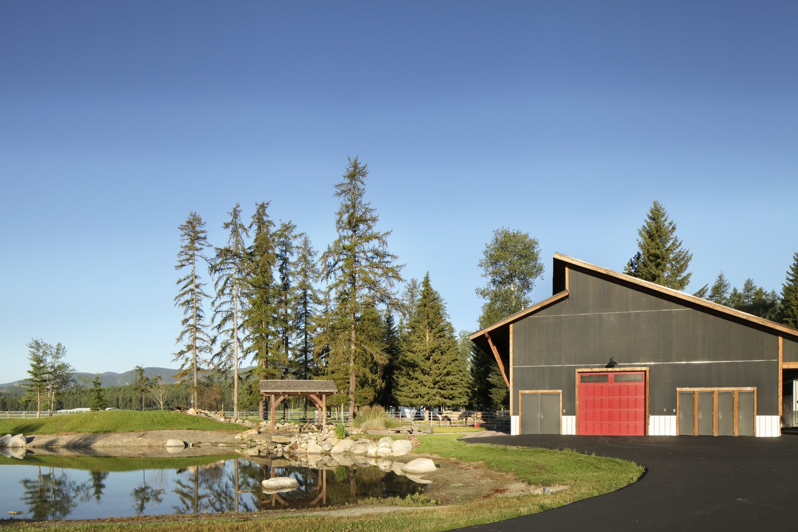 The outdoor arena is currently paved for vehicle storage, but it can be retrofitted to become a working riding ring. Tagged: Outdoor, Back Yard, Woodland, and Trees.  Photo 10 of 11 in A Rock & Roll Hall of Famer's Picturesque Montana Retreat Is Going Up For Auction