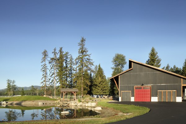 Modern home with outdoor, back yard, woodland, and trees. The outdoor arena is currently paved for vehicle storage, but it can be retrofitted to become a working riding ring. Photo 10 of 534 Twin Bridges Road