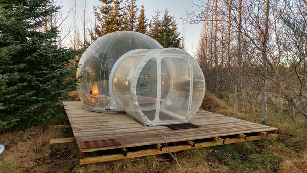 Smaller bubbles come with a round bed that sleeps two, while the larger units have a double bed. Guests share a wood-clad outbuilding that holds the restroom, showers, and kitchen. Adventurers can also book the Golden Circle Tour through Buubble, exploring Thingvellir National Park, the Geysir hot springs, Gullfoss waterfall, and the Secret Lagoon before spending a night at the hotel.  Photo 1 of 6 in Sleep Under the Northern Lights in an Icelandic Bubble Hotel