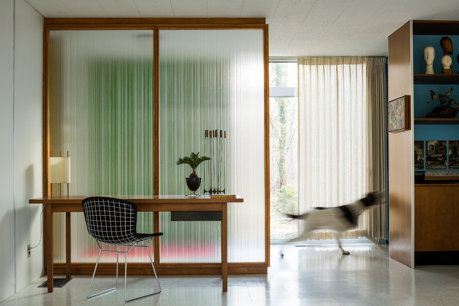 A Paul McCobb reeded glass panel provides a contemplative backdrop for a walnut Knoll writing desk and Bertoia Side Chair. Tagged: Office, Desk, Chair, Lamps, and Terrazzo Floor.  Photo 3 of 14 in A Rare Midcentury Prefab Looks Just Like it Did in 1958—Down to the Knoll and Paul McCobb Interiors