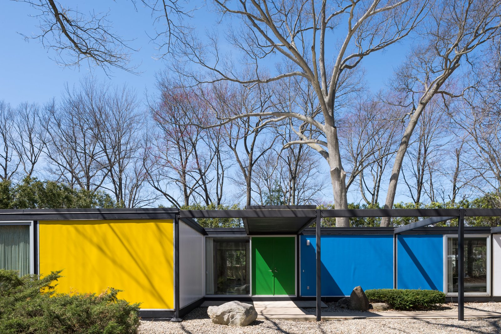 Built with a steel frame, the Frost House features panels of styrofoam between aluminum sheets for the exterior walls and styrofoam between plywood for the roof and floors. Bold, primary colors accentuate its geometric form. Tagged: Outdoor, Front Yard, and Small Patio, Porch, Deck.  Photo 2 of 14 in A Rare Midcentury Prefab Looks Just Like it Did in 1958—Down to the Knoll and Paul McCobb Interiors