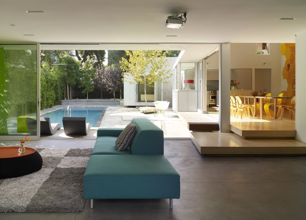 Modern home with living room, sofa, and concrete floor. Photo  of Norwich Drive Residence