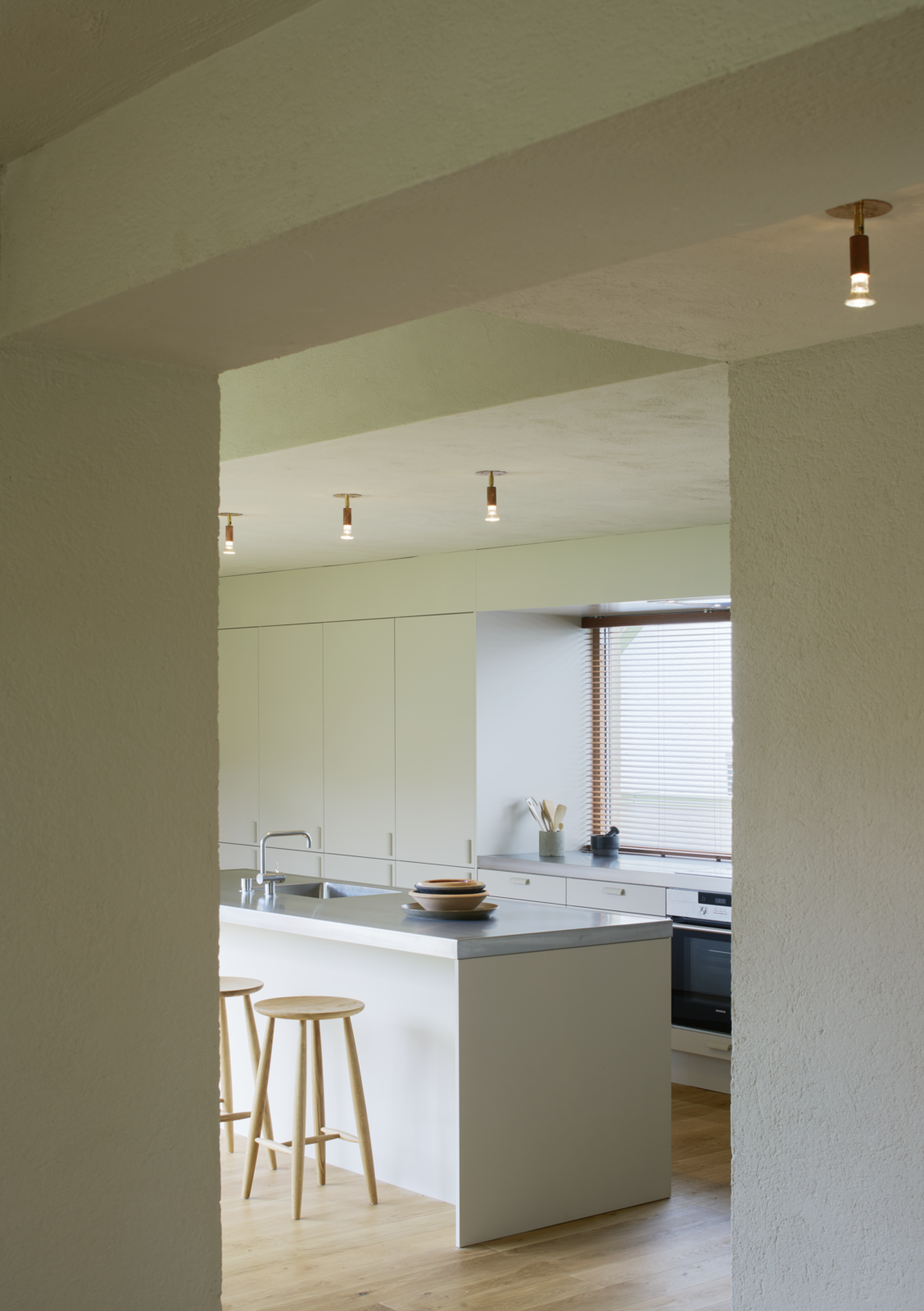 Tagged: Kitchen, Medium Hardwood Floor, and White Cabinet.  Photo 6 of 12 in Sleek Scandinavian Design Permeates a Family's Summer House in an Old Fishing Village